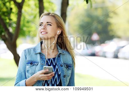 Young woman listening to music and walking in the park