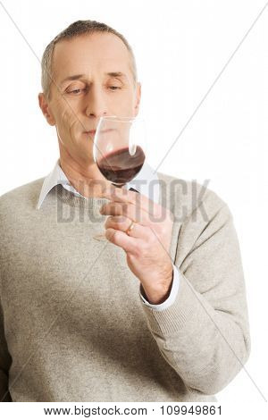 Handsome mature man tasting red wine.