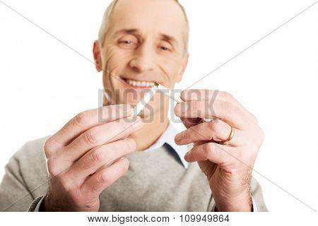 Successful mature man with broken cigarette.