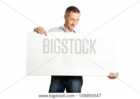 Handsome mature man holding an empty banner.