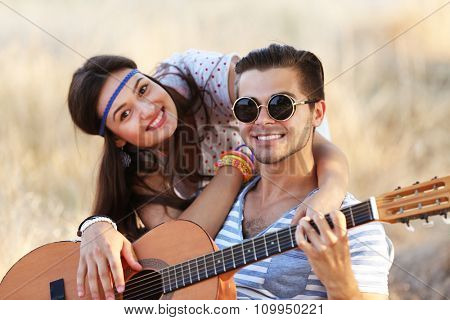 Attractive couple playing guitar, outdoors