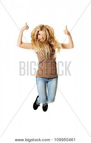 Young casual teenager jumping with thumbs up.