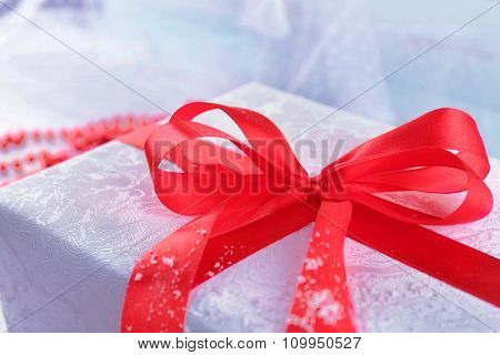 Beautiful gift with bow on color wooden background