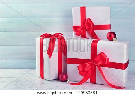 Beautiful gifts with bows on color wooden background