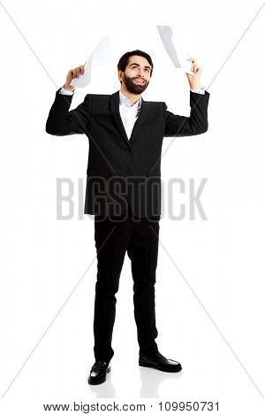 Happy young businessman throwing paper sheets.