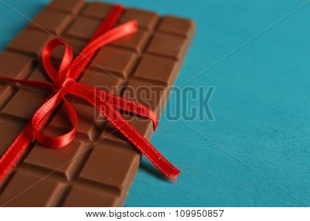 Milk chocolate bar with red bow on color wooden background
