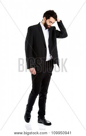 Young depressed businessman holding his head.