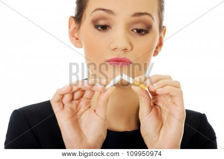 Beautiful businesswoman breaking cigarette to quit smoking.