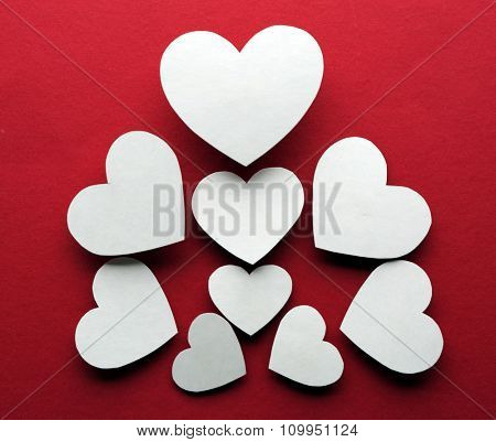 White paper hearts on dark pink background