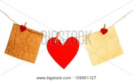 Paper hearts and empty sheet hang on cord isolated on white background
