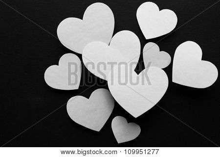 White paper hearts on  black background