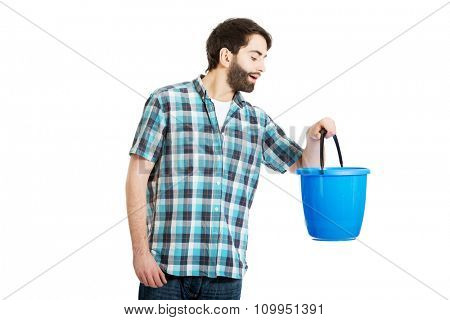Young handsome man looking into plastic blue bucket.