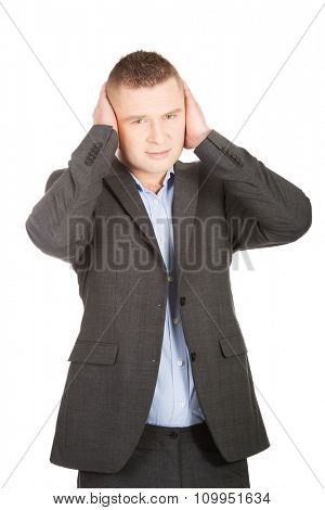 Young businessman suffering from headache.