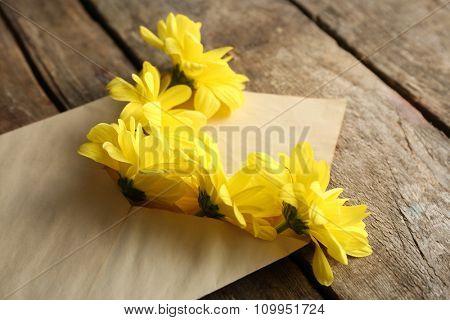 Yellow chrysanthemum in envelope on wooden background
