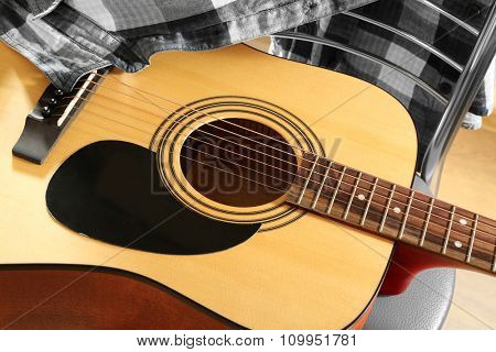 Acoustic guitar with checkered shirt on red stool background
