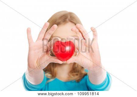 Teenage woman holding heart model
