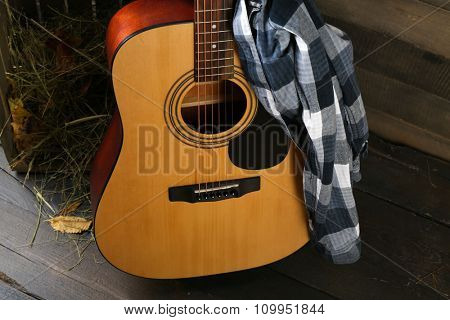 Acoustic guitar and blue checkered shirt against box with hay on wooden background, close up