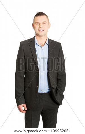 Young smiling businessman with hand in pocket.