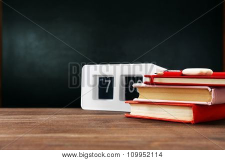 Books and clock on desk background