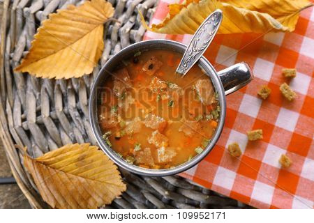 Mug of soup on wicker mat closeup