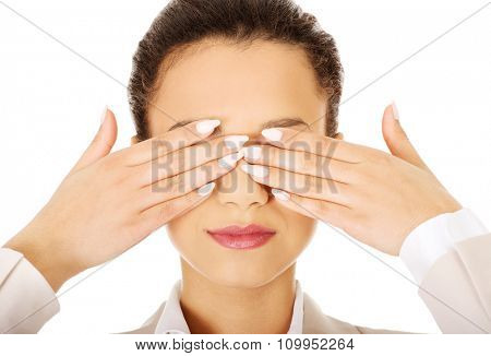African businesswoman covering eyes with hands.