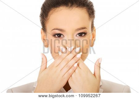 African businesswoman covering mouth with hands.