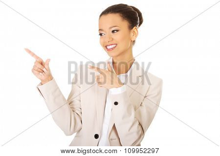 Happy african businesswoman pointing up.
