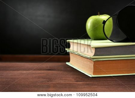 Apple and books, magnifier on desk background