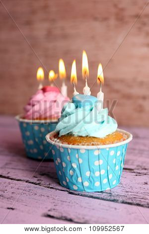 Tasty cupcakes with candles on violet table against wooden background, close up