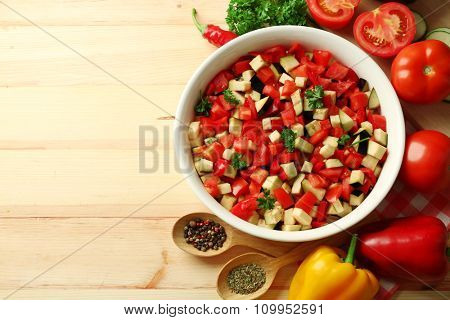 Ratatouille before cooking and ingredients, on wooden background