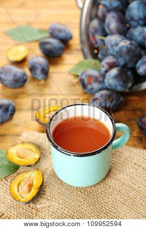 Plum Juice in mug with fresh fruits