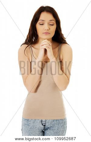 Young woman praying with her hands together and eyes closed.