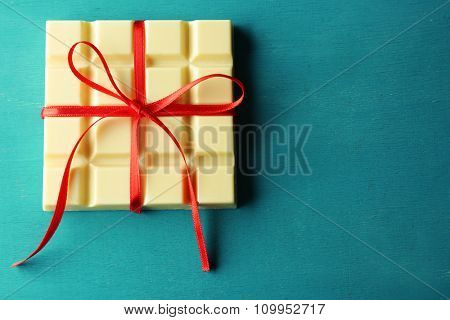 White chocolate bar with red bow on color wooden background