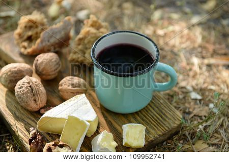 Mug with red wine, delicious cheese and nuts on wooden board outdoors - picnic theme