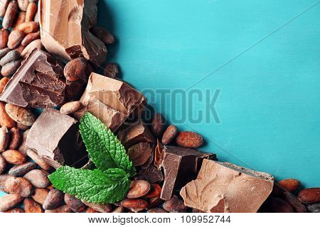 Dark and milk chocolate pieces and cocoa beans on color wooden background