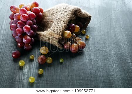 Juicy purple grapes in sack pouch, on wooden background