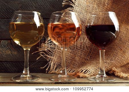 Composition of wine glasses on wooden background