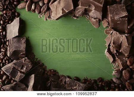 Black and milk chocolate pieces and coffee grains on color wooden background