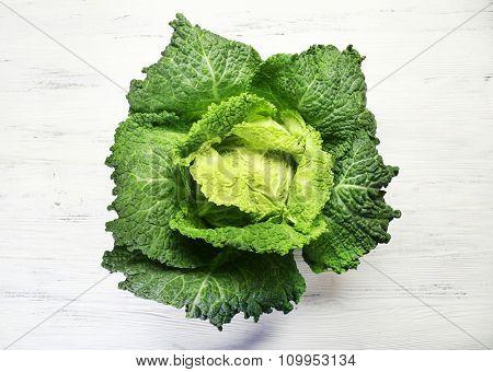 Savoy cabbage on light wooden background