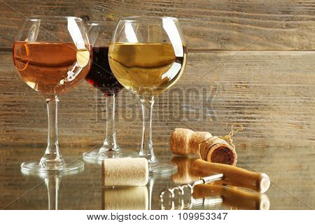 Wine glasses, corks and screw on wooden background