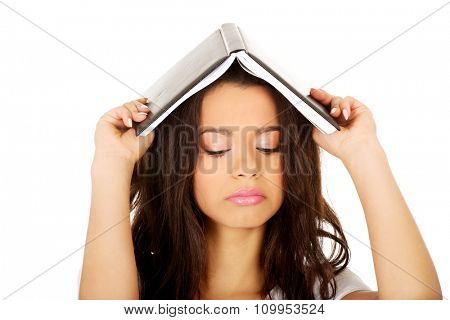 Unhappy student woman with a book on head.