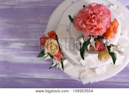 White wedding cake decorated with flowers on grey  wooden background