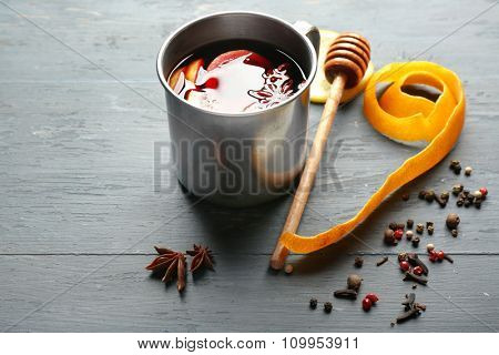 Mulled wine in a mug with citruses on grey wooden background, close up