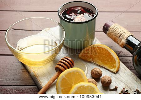 Traditional mulled wine in a mug on decorated wooden background, close up