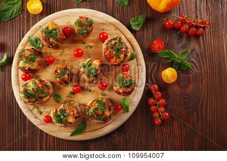 A wooden tablet with stuffed mushrooms and vegetables on the table, top view
