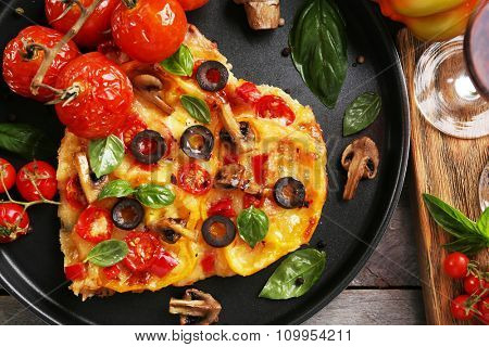 Decorated pizza with vegetables on pan on wooden background
