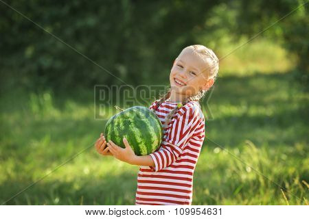 Small girl with watermelon on lawn