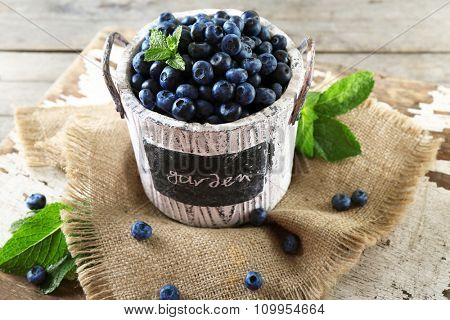 Tasty ripe blueberries with green leaves in bucket on table close up