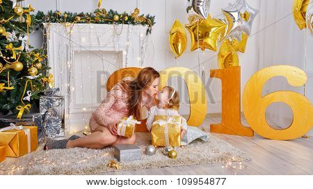 Mother Kissing Daughter. New Year 2016.