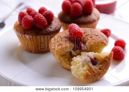 Delicious cupcakes with berries on plate close up